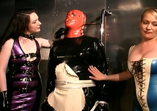 Two beautiful mistresses dress their serf up in latex