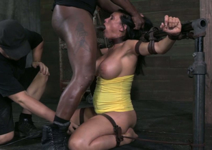 Belted brunette in yellow dress is belted and stands on knees while giving BJ