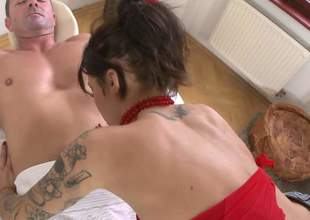 Tattooed brunette Nikita Bellucci in red and black stockings teases a guy on massage table and then pulls her pants aside. She displays her pink pussy and fingers her asshole